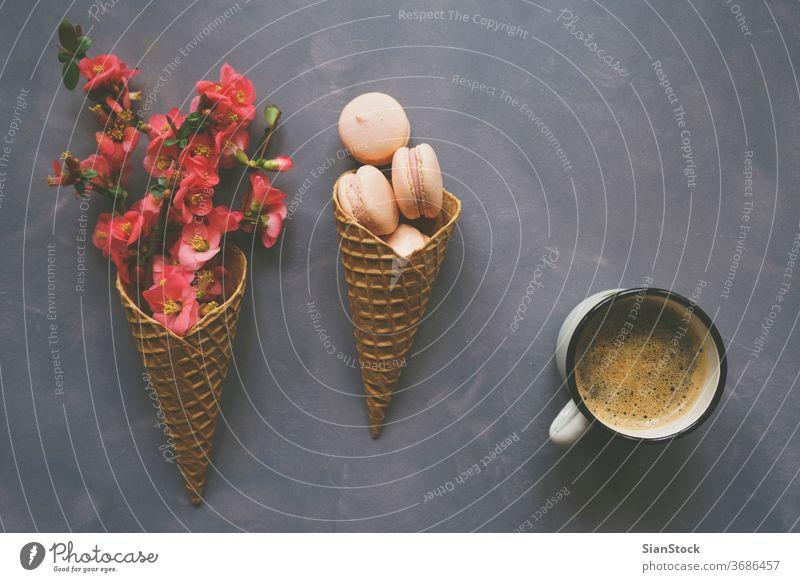 Kaffee, Makronen und Blumen in Eistüte auf Zementhintergrund Morgen Top Macaron Ansicht Tisch Tasse weiß Hintergrund legen flach Schreibtisch rosa Frühstück