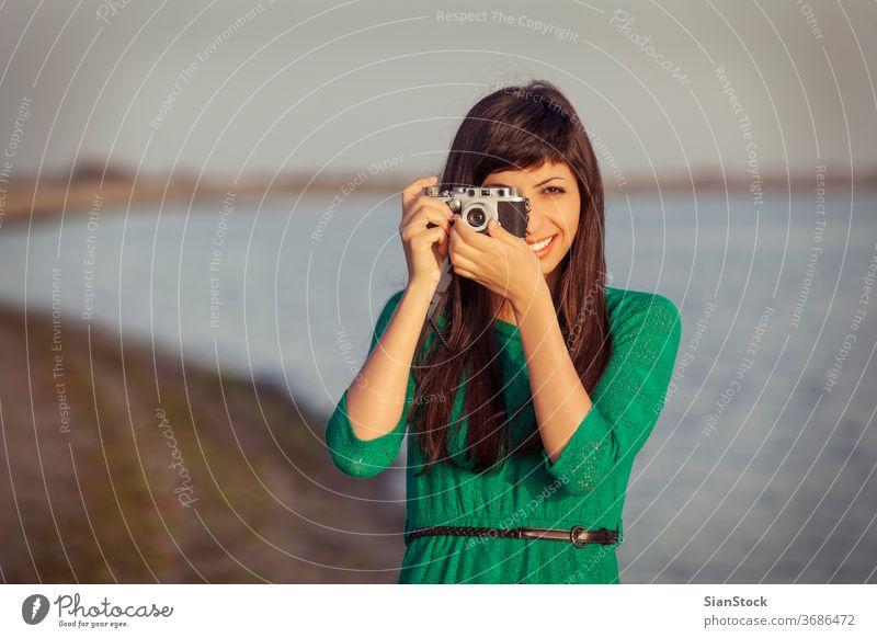 Vintage-Foto, brünettes Mädchen mit Retro-Kamera Strand Fotokamera altehrwürdig retro Meer Urlaub Menschen Sommer reisen blau Fotograf Mode Lifestyle Feiertag