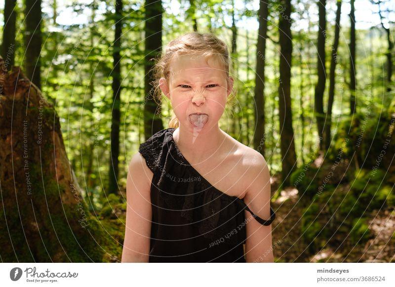 Wildes Mädchen im Wald streckt die Zunge raus wild Porträt Kind Kindheit Kindheitserinnerung Kindererziehung Spielen Außenaufnahme Freude