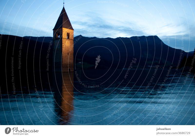 Kirche im Reschensee Kirchturm Kirchturmspitze See abgesoffen unter Wasser Überschwemmung Turmuhr Hochwasser Abendstimmung spiegeln Abenddämmerung Untergang