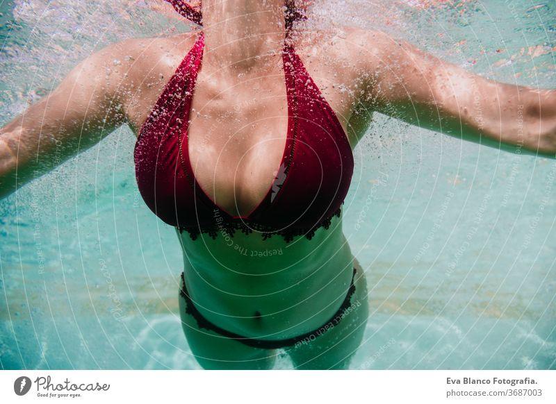 Nahaufnahme einer jungen Frau, die in einem Schwimmbad unter Wasser taucht. Sommer und lustiger Lebensstil abschließen Schwimmsport Blasen Spaß Kaukasier Pool