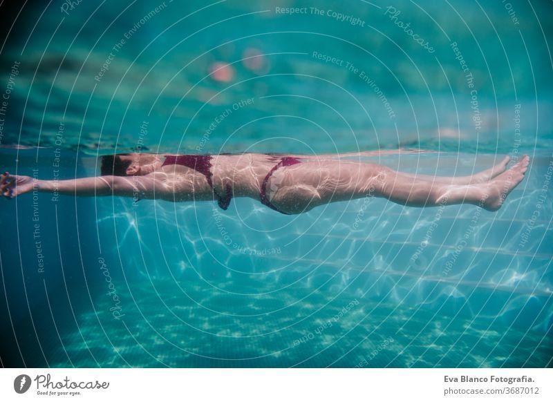 junge frau schwimmt in einem schwimmbad. sommer und lebensstil Frau unter Wasser Schwimmsport Sommer Blasen Spaß Kaukasier Pool Sinkflug Lifestyle übersichtlich