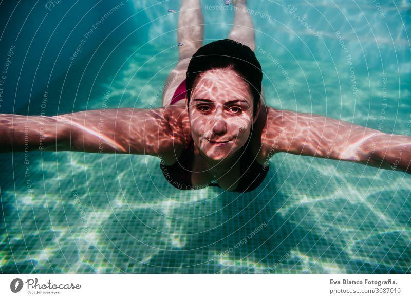 junge Frau, die in einem Schwimmbad unter Wasser taucht. Sommer und lustiger Lebensstil Schwimmsport Blasen Spaß Kaukasier Pool Sinkflug Lifestyle übersichtlich