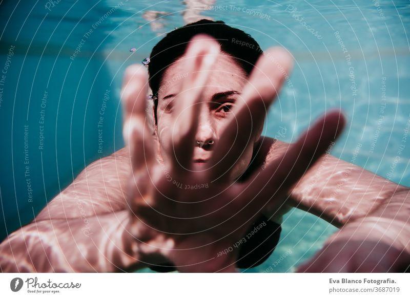 Porträt einer jungen Frau, die in einem Schwimmbad unter Wasser taucht. Sommer und lustiger Lebensstil berührend Hand Schwimmsport Blasen Spaß Kaukasier Pool