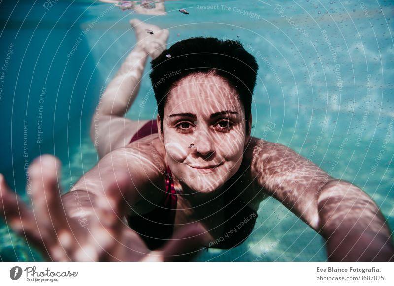 Porträt einer jungen Frau, die in einem Schwimmbad unter Wasser taucht. Sommer und lustiger Lebensstil abschließen Schwimmsport Blasen Spaß Kaukasier Pool
