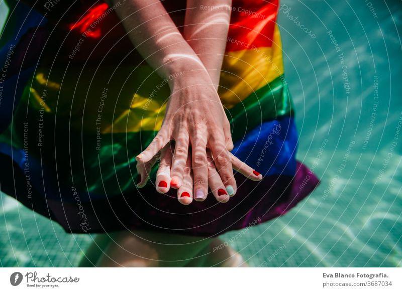 zwei Frauen am Pool zusammen mit einer regenbogenfarbigen Schwulenfahne umwickelt. LGBT-Konzept Liebe lesbisch Schwulenflagge unter Wasser Schwimmbad