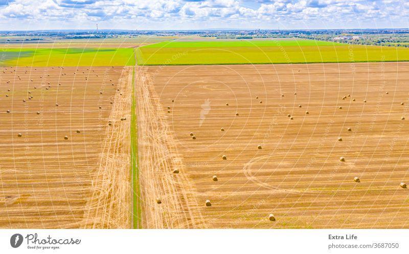 Luftaufnahme einer schmutzigen Straße zwischen landwirtschaftlichen Feldern oben quer Antenne Ackerbau unter Unter Ballen Borte Müsli einlochen Landschaft Ernte