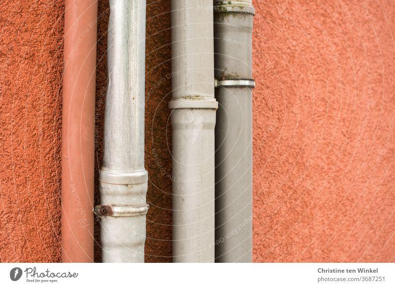 Fallrohre vor einer orange verputzten Wand, ein orangefarbenes und drei graue Fassade Haus Strukturen & Formen Detailaufnahme Putz Gebäude Abwasser