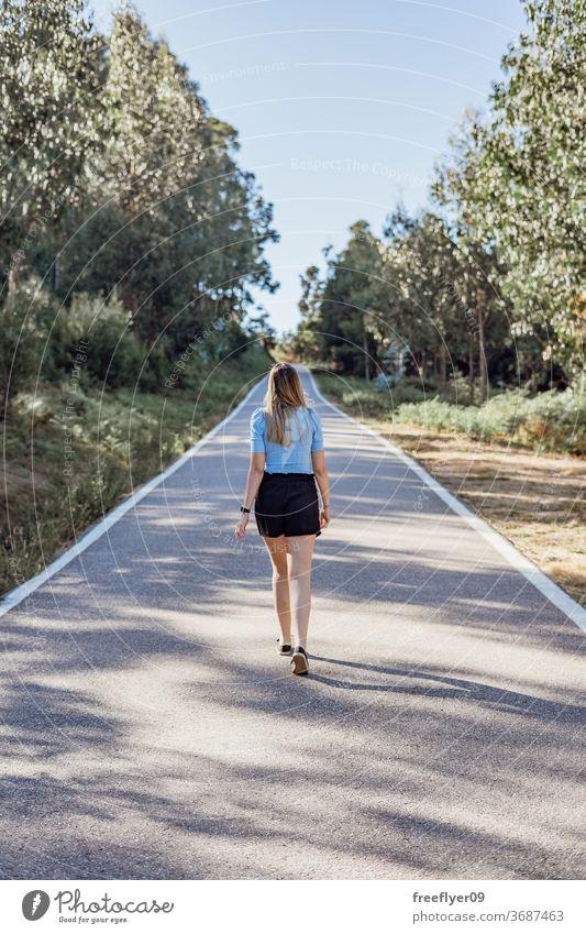 Junge kaukasische Frau geht an einer leeren Straße in der Nähe eines Waldes laufen Lifestyle Textfreiraum Landschaft Mode Model jung blond Kaukasier Sonnenlicht