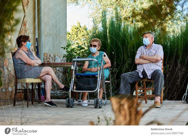 Gruppe von älteren Menschen sitzen auf der Terrasse des Hauses Senior Großeltern sich[Akk] sammeln Hof Zusammensein alt Mundschutz Coronavirus behüten COVID