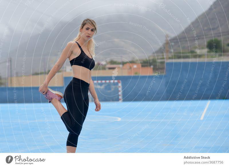 Schlanke Sportlerin streckt die Beine auf dem Sportplatz Frau Training Übung Dehnung Fitness Athlet Läufer schlank jung modern Wellness Wohlbefinden Gesundheit