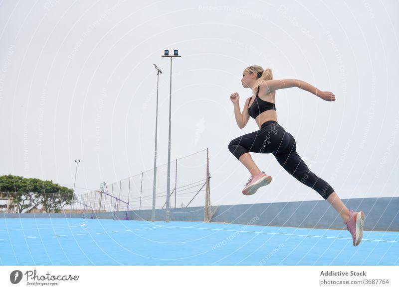 Schlanke Sportlerin springt auf Sportplatz Frau springen laufen Training Übung Fitness Athlet schlank jung modern Wellness Wohlbefinden Gesundheit Lifestyle