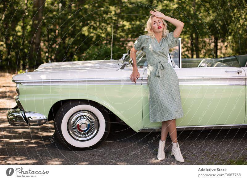 Charmante Blondie in der Nähe von Retro-Auto auf der Straße Frau PKW retro altehrwürdig blond Stil jung Fahrzeug klassisch Blondine Lifestyle trendy
