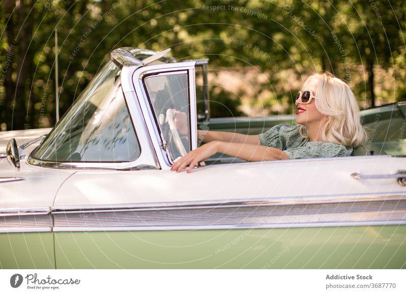 Glückliche Frau fährt Retro-Auto Fahrer PKW retro Sommer Lächeln sonnig tagsüber blond Stil positiv Sonnenbrille altehrwürdig Fahrzeug Verkehr Freude Reise