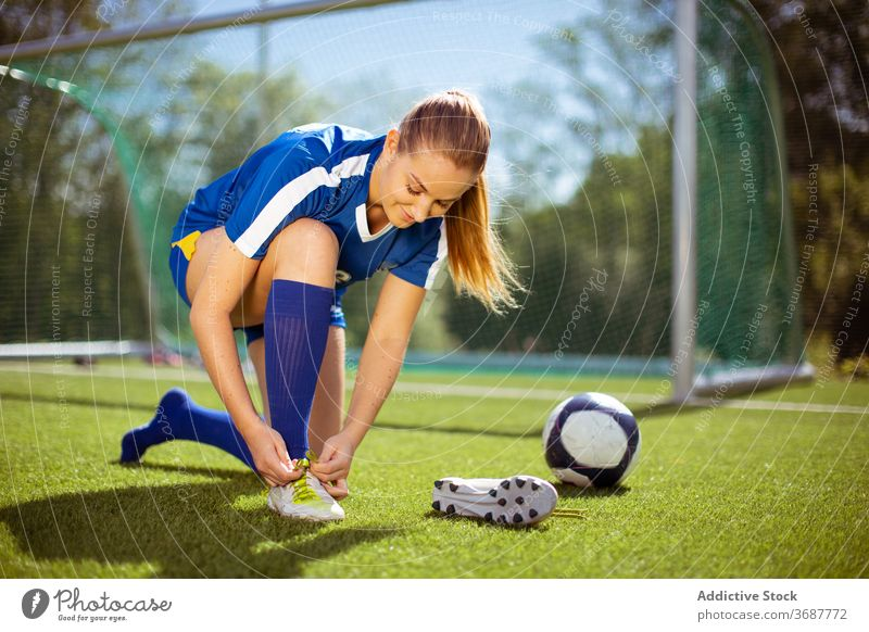 Positive Sportlerin beim Binden der Fußballschuhe Krawatte Stiefel Training vorbereiten positiv angezogen Feld Frau Athlet Ball Tor Sportbekleidung Gesundheit