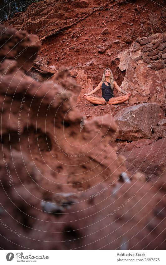 Frau in einem Badeanzug sitzt in der Meditation in einem trockenen Terrain quer vertikal bleiben Ruinen Gelände Oberfläche vereinzelt Verlassen Yoga Natur