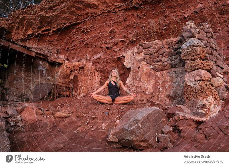 Frau in einem Badeanzug sitzt in der Meditation in den Ruinen eines Hauses in einem trockenen Terrain antik bleiben Gelände Oberfläche vereinzelt Verlassen Yoga