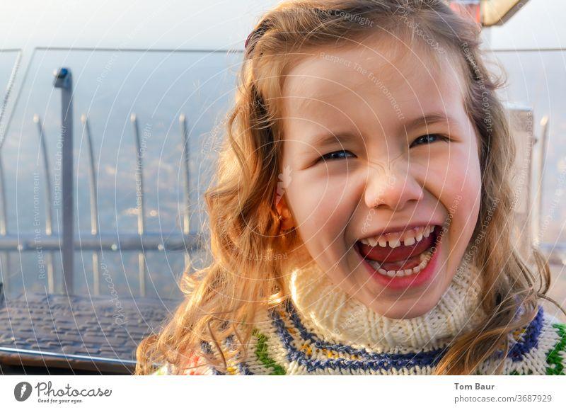 Portrait eines lachenden blonden Mädchens porträt portrait Blick in die Kamera Lachen fröhlich spass lustig locken lockiges haar blondes haar blaue augen