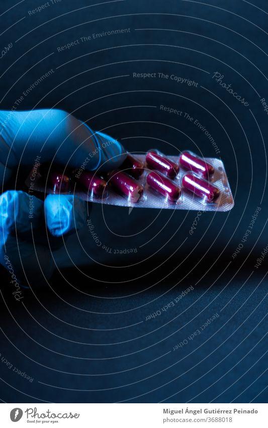 Vertikale Aufnahme der Hand einer Person in einem blauen Plastikhandschuh mit roten Pillen. Handschuhe Körperpflege covid-19 COVID Rote Pillen Coronavirus