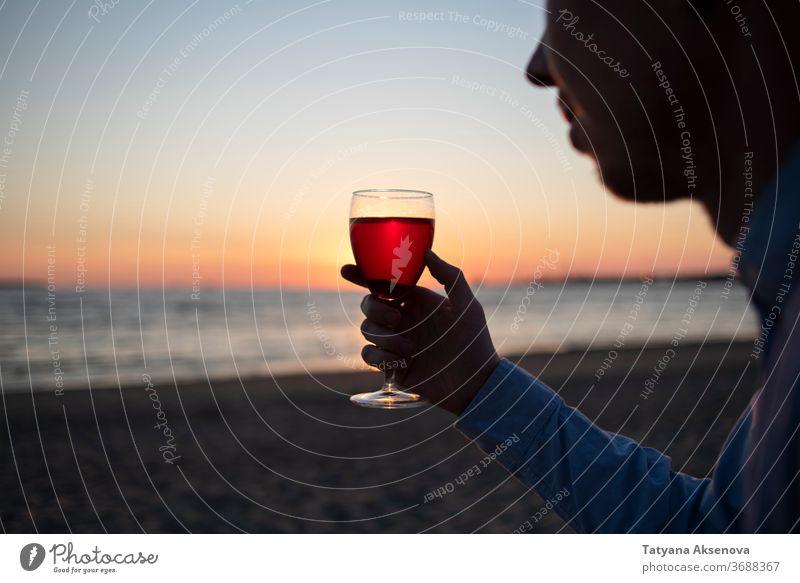 Mann mit einem Glas Wein am Strand bei Sonnenuntergang trinken Alkohol romantisch genießend langsames Leben sich[Akk] entspannen MEER schön Feier Getränk