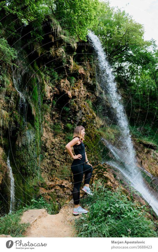 Junge Naturforscherin steht am Wasserfall Errungenschaft aktiv Erwachsener Abenteuer Ehrfurcht Kaskade Kaukasier Ausflugsziel genießend Genuss Umwelt Erkundung