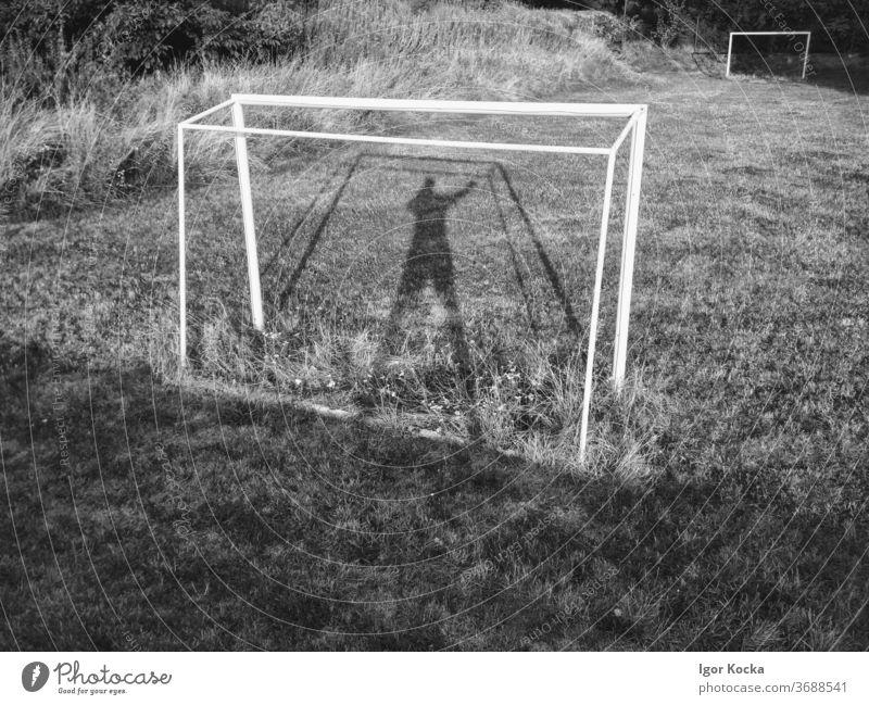 Fussballtor auf leerem Fussballfeld Fußballtor Fußballplatz Fußballfeld Schatten Torwart vergangen Menschenleer veraltet bewachsen Sport Ballsport