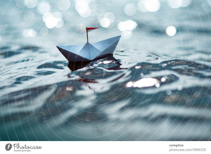 Kleines Papierschiff auf glitzerndem See Sonnenstrahlen Sonnenlicht Lichterscheinung Reflexion & Spiegelung Farbfoto glänzend Reisefotografie Ziel Segelboot