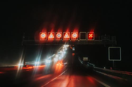 Reflexionen von Straßenschildern und Autos bei Nacht Asphalt Autobahn Unschärfe verschwommen PKW gefährlich dunkel Laufwerk fahren Fernstraße beleuchtet Reise