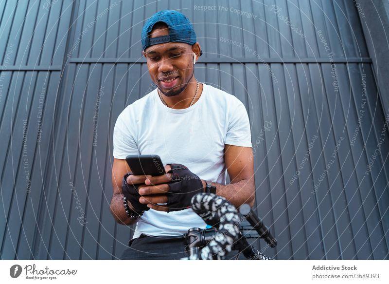Heiterer ethnischer Mann mit Smartphone und Kopfhörern Biker Ohrstöpsel zuhören Musik Glück modern benutzend urban Stil Hipster Fahrrad trendy jung Handy
