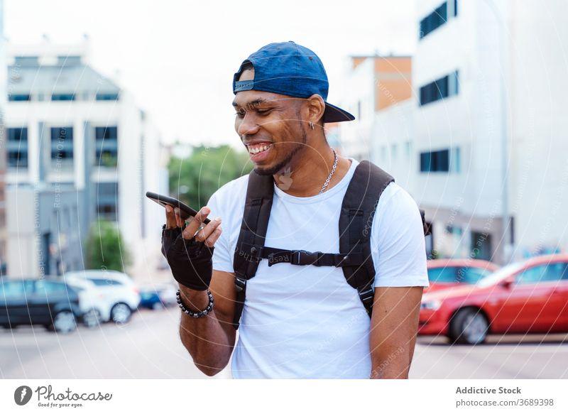 Glücklich ethnischen Mann mit Smartphone auf der Straße benutzend Kommunizieren Stil urban Biker Nachricht modern trendy heiter Optimist Lifestyle Hipster