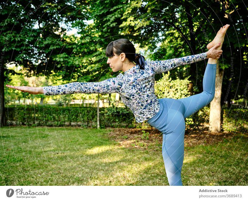 Frau macht Yoga in Lord of the Dance Pose im Park Herr des Tanzes beweglich Asana Natarajasana Konzentration Windstille Natur Gesundheit üben sonnig Harmonie