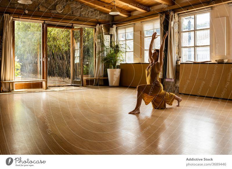Frau macht Yoga in Crescent Lunge Pose üben Sichel-Lungen-Pose anjaneyasana Atelier Wellness Kleid Konzentration Gesundheit schlank Asana Harmonie