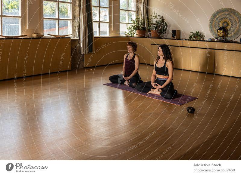 Frauen meditieren gemeinsam im Studio Yoga Lotus-Pose Achtsamkeit üben padmasana Weihrauch Aroma kleben Atelier ruhig Asana Harmonie Wellness Windstille