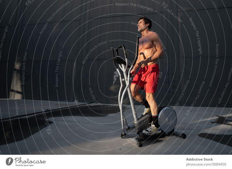 Sportler trainiert auf Stepper auf der Straße Maschine Übung Herz Training Großstadt elliptisch Athlet männlich muskulös stark nackter Torso ohne Hemd passen