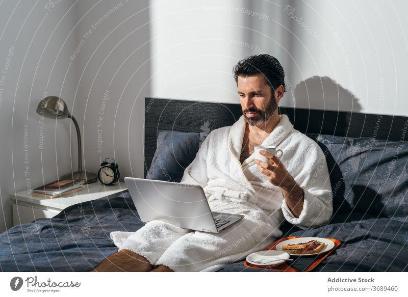 Ruhiger Mann beim Frühstück im Bett freiberuflich Kaffee Laptop Arbeit abgelegen Bademantel benutzend männlich Geschäftsmann Tasse frisch Morgen trinken Gerät