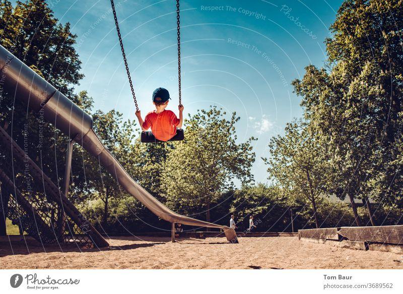 Junge auf Schaukel auf dem Spielplatz Kind schauckeln Spielen hoch Kette Abenteuer tollkühn Mütze von hinten Rutsche spaßig Spaß haben Bäume Sand Sandkasten