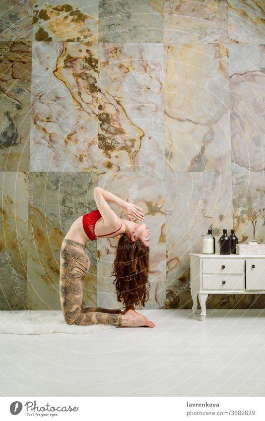 Junge weibliche Yogapraktizierende Ustrasana-Kamel-Positionsvariante im Haus Frau Sport Fitness Kamel-Pose Hatha Ashtanga Zen ustrasana schlank dünn aktiv
