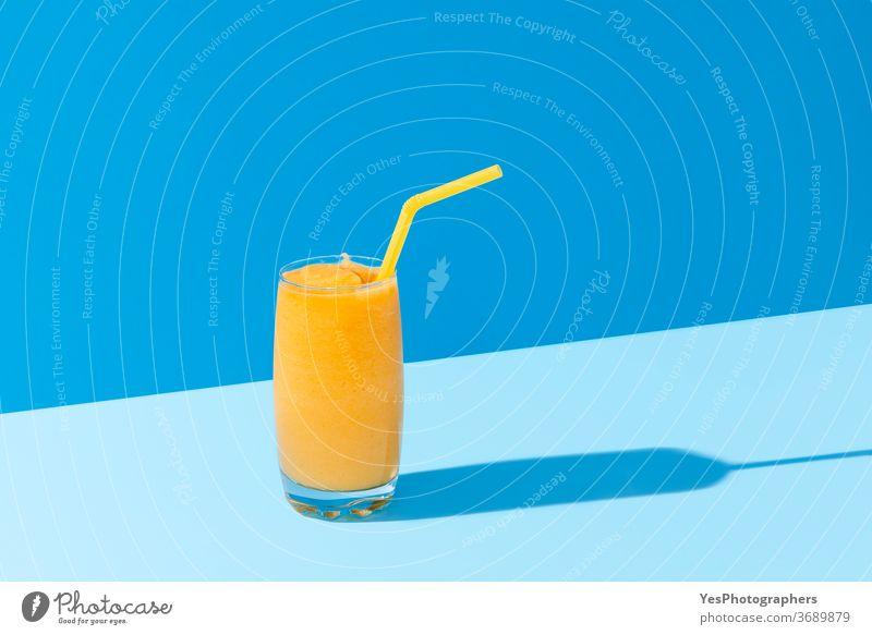 Mango-Smoothie auf blauer Farbe. Sommerliches Getränk. Mangoshake mit Strohhalm Hintergrund hell Cocktail kalt Farben Textfreiraum ausschneiden lecker Dessert