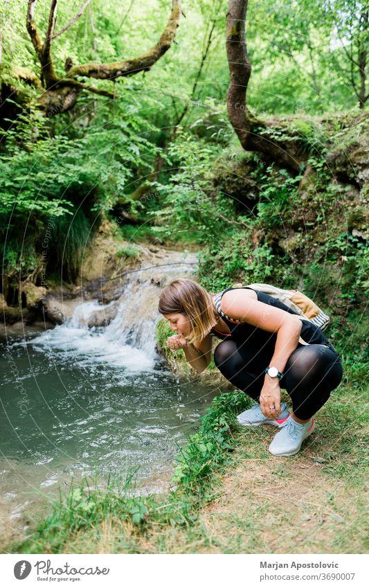 Junge weibliche Naturforscherin trinkt Wasser aus der Quelle aktiv Aktivität Erwachsener Abenteuer Rucksack Backpacker Bach trinken Ökologie erkunden Entdecker