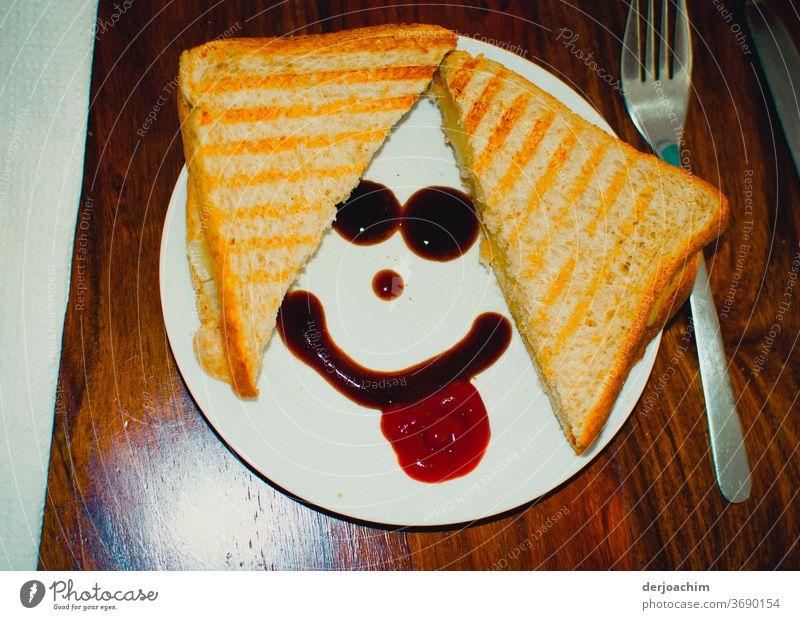 Frühstück Smiley, Ein geteiltes Brot auf dem Teller. Mit Ketschup ein Smiley. Rechts eine Gabel auf einem Holztisch. frühstück snack Lebensmittel Farbfoto