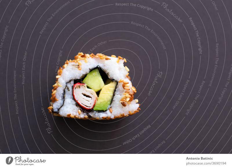 Nahaufnahme eines einzelnen Stückes einer hausgemachten, nicht perfekten Sushi-Rolle. Isoliert auf dunkelschwarzen Hintergrund. Rolle mit Avocado, Surimi, Gurke und gebratenen Sesamkörnern