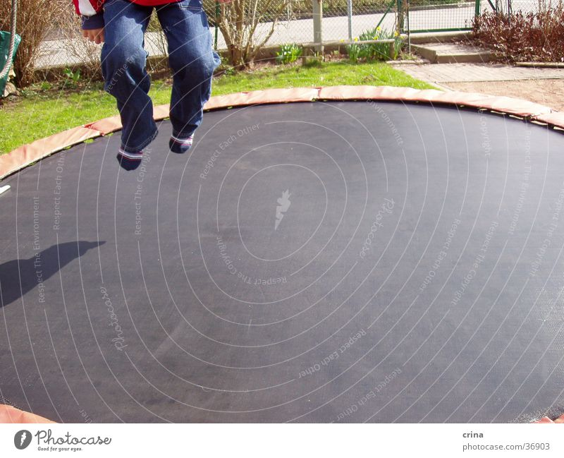 ... und hop... Mann springen Fuß Beine Jeanshose hüpfen Trampolin Sport
