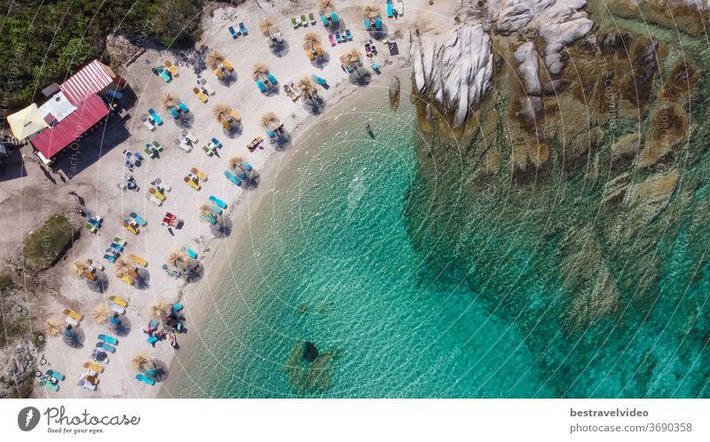 Griechisch-mediterrane Landschaftsdrohne mit Badegästen am Strand von Kavourotripes erschossen. Luftaufnahme der Halbinsel Sithonia Chalkidiki mit felsiger Küste, kristallklarem Wasser und Meeresgrund mit Sonnenschirmen.