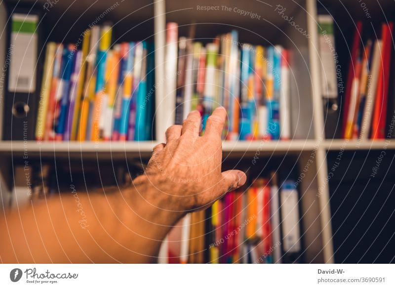 Griff ins Bücherregal lesen Literatur lernen üben Prüfung & Examen Lehrbuch Schule Studium nachlesen nachschlagen Wissen wissensdurstig Student zu Hause Buch