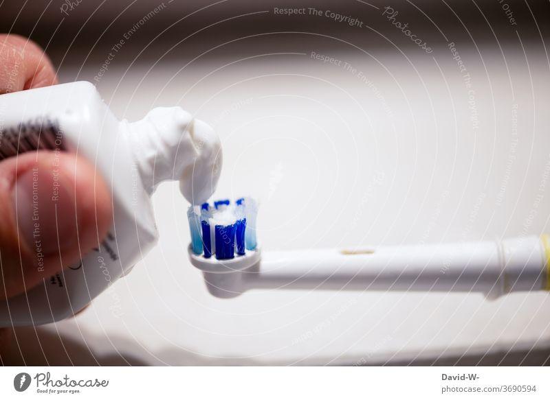 Zahnpasta für die Zahnbürste Zahn der Zeit Zahnarzt Zahnpflege Zahnmedizin Finger Hand drücken Zahncreme Textfreiraum oben Starke Tiefenschärfe