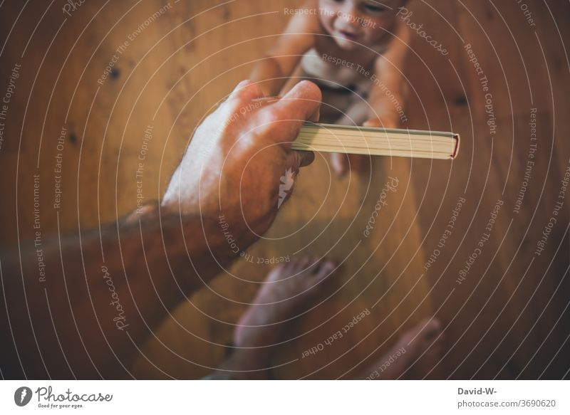 Kleinkind fordert den Papa auf ein Buch zu lesen Kind Aufforderung auffordern Kindererziehung Fürsorge Bücher Kinderbücher Boden Vogelperspektive Hand greifen