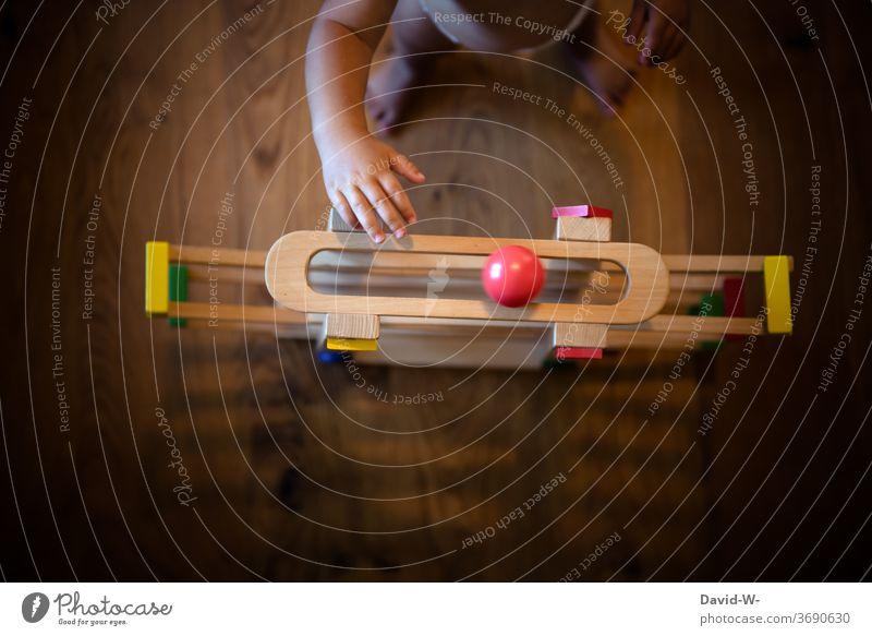 Kind spielt mit seinem Spielzeug spielen Kinderzimmer Kleinkind stehen benutzen greifen jung niedlich anonym tasten Finger Hände Kugel Spielen Kindheit Freude