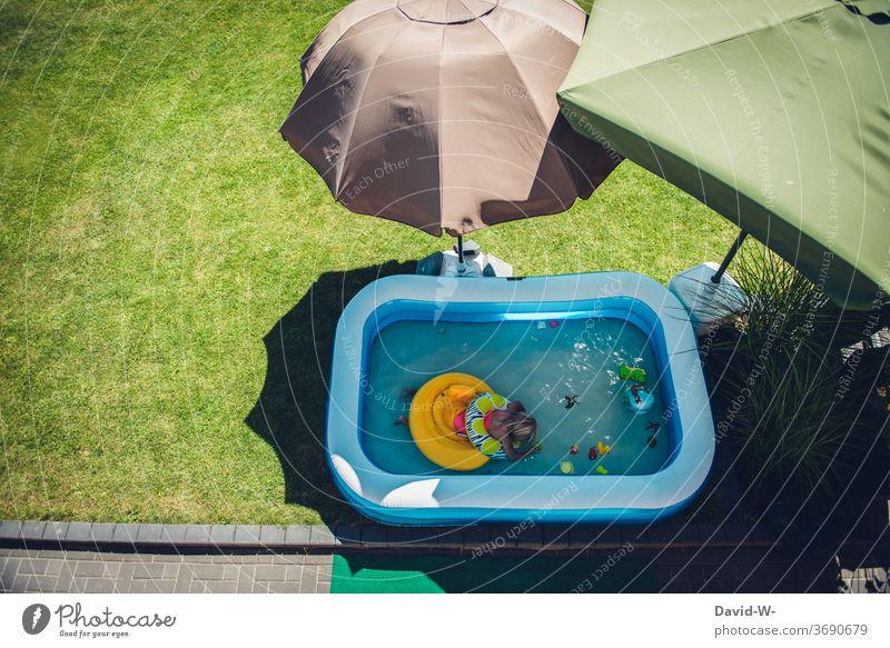 Kind badet im Garten in einem Planschbecken umringt von Sonnenschirmen die Schatten spenden schattenspender Sonnig Quarantäne Eigenheim Kindheit Mädchen baden