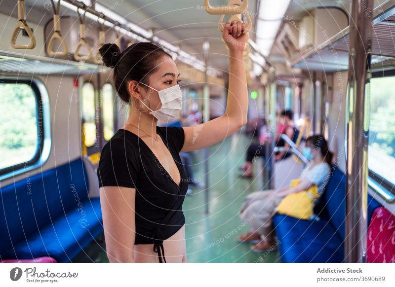 Asiatische Frau in Maske im Zug reisen Mundschutz Coronavirus Öffentlich Verkehr Ausbruch behüten Arbeitsweg ethnisch asiatisch modern Passagier stehen Ausflug