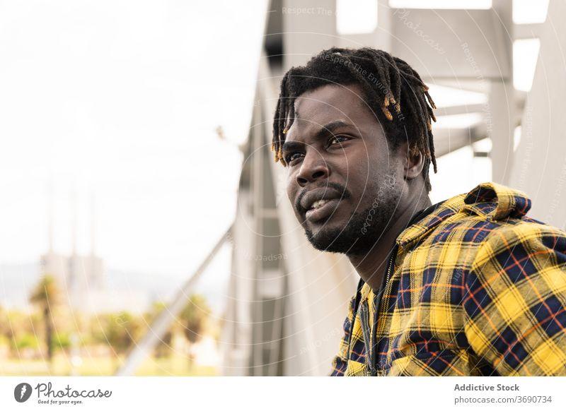 junger afrikanischer Mann mit einer Struktur im Hintergrund Person Afrikanisch urban Lebensstile schwarz männlich Amerikaner Porträt Typ Glück gutaussehend